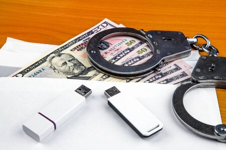 Envelope with an American Dollars Handcuffs and Two USB Drives on the Table closeup Фото со стока