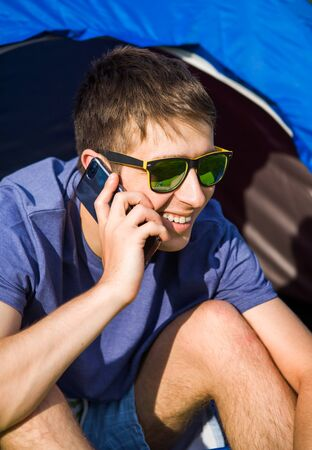 Young Man speaking by the Phone in the Tent on the Nature