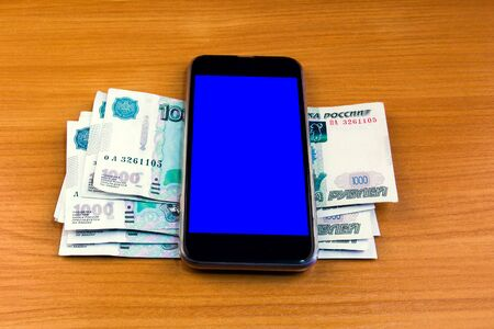 Russian Rubles and Mobile Phone on the Wooden Table closeup