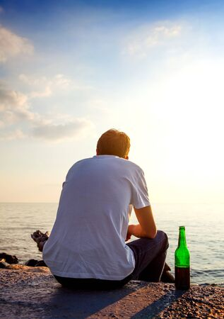 Young Man with a Beer sit at Seaside on Sunset Background Stok Fotoğraf