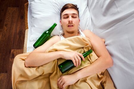 Young Man sleep with a Beer Bottle in the Bed at the Home