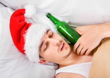 Man in Santa Hat sleeping in the Bed with a Beer