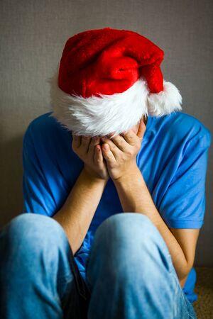 Hombre triste con gorro de Papá Noel esconde un rostro junto a la pared Foto de archivo