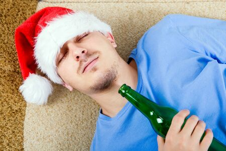 A Man in Santa Hat sleeping on the Sofa with a Beer