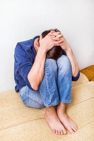 Triste jeune homme sur le canapé dans la chambre