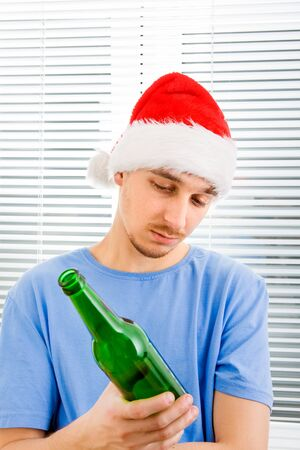 Young Man in Santa Hat looking on a Bottle of the Beer on the Jalousie Background