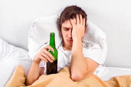 Sad Young Man with a Beer Bottle in the Bed at the Home