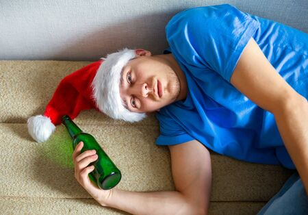 Young Man in Santa Hat on the Sofa with a Beer Фото со стока