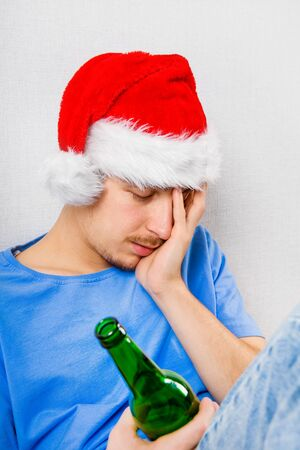 Sad Young Man in Santa Hat with a Beer by the Wall Stock Photo
