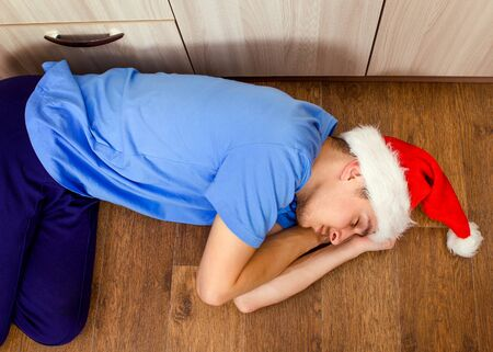 Young Man in Santa Hat sleeping on the Floor at the Home