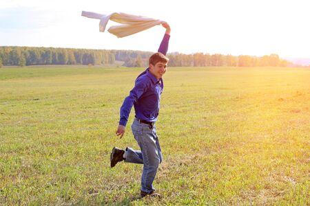 Heureux jeune homme courant sur l'herbe du champ d'été Banque d'images