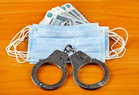 Medical Flu Mask Handcuffs and Russian Rubles on the Wooden Table closeup