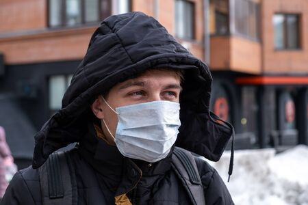 Young Man in the Flu Mask on the City Street Portrait closeup
