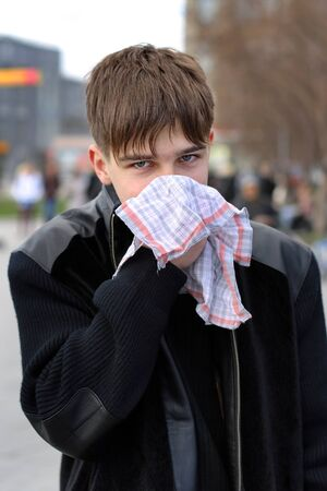 Teenager with a Flu hold a Handkerchief in the City Street Stock fotó