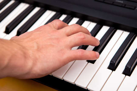 Hand and Piano Keyboard in the Room closeup