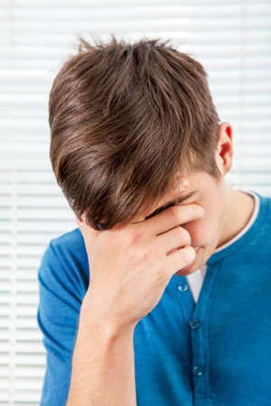 Sad Young Man in the Room on the Jalousie Background Stock Photo