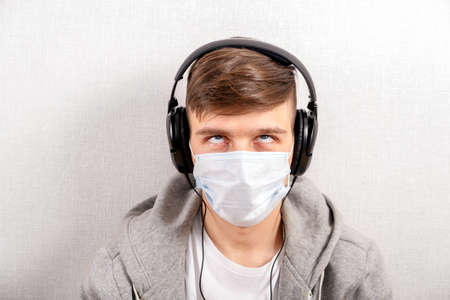 Irritated Young Man in Headphones and Flu Mask by the Wall in the Room Reklamní fotografie