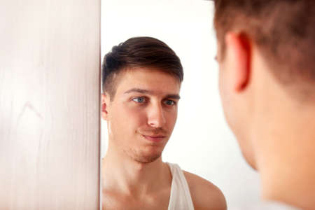 Young Man looking to Reflection in the Mirror in the Room