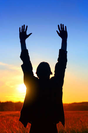 Happy Man Silhouette with Hands Up on the Sunset Background outdoor Stock Photo