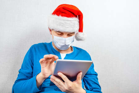 Young Man in Santa Hat and Flu Mask with a Tablet Computer by the White Wall