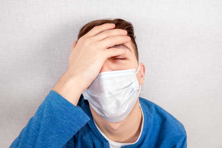 Painful Young Man in a Flu Mask by the Wall in the Room