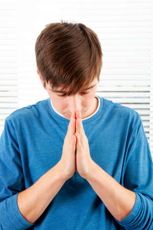 Young Man is Praying on the Jalousie Background