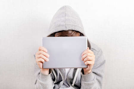 Person in a Hoodie behind a Tablet Computer by the Wall