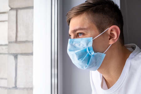 Young Man in a Flu Mask by the Window in the Room