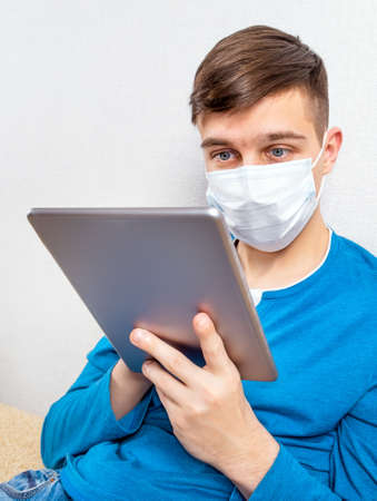 Young Man in Flu Mask with a Tablet by the Wall in the Room 版權商用圖片