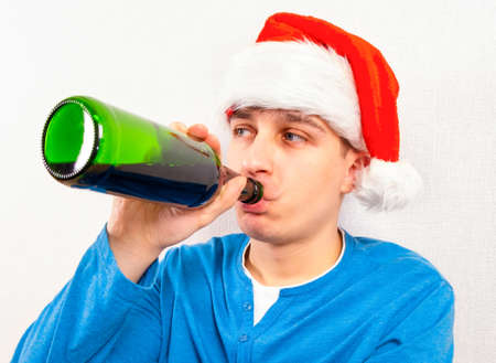 Young Man in Santa Hat drink a Beer by the Wall in the Room