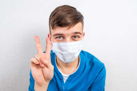 Happy Young Man in a Flu Mask show a Victory Gesture by the Wall in the Room