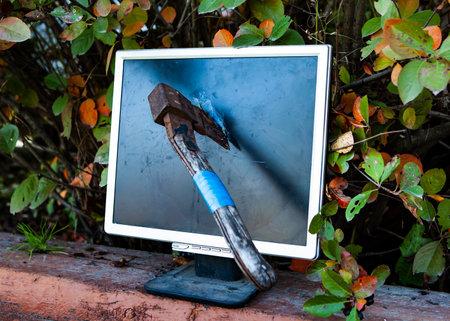 Axe to Smash a Computer Screen Monitor outdoor closeup