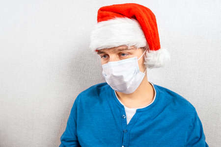 Sad Young Man in Santa Hat and Flu Mask by the Wall in the Room 版權商用圖片