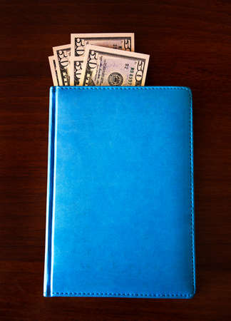 Money in the Book on the Wooden Table closeup