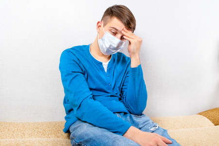 Sad and Tired Young Man in a Flu Mask by the Wall in the Room