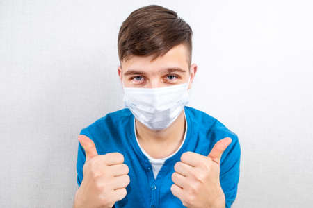 Happy Young Man in a Flu Mask show a Thumb Up Gesture by the Wall in the Room