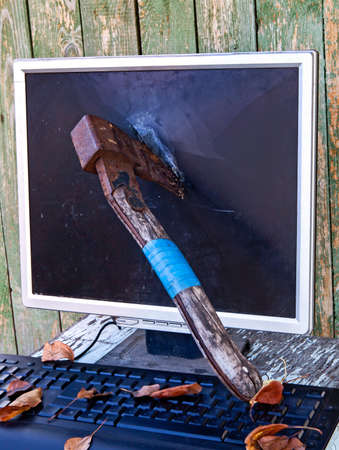 Axe in a Computer Screen Monitor on the Old Planks Background outdoor