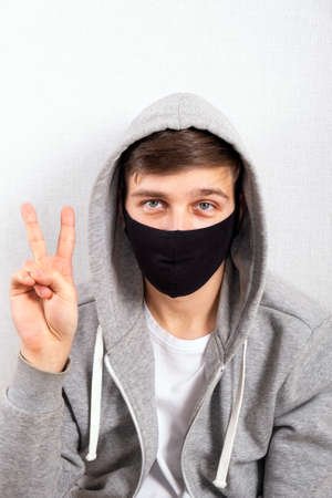 Young Man in a Flu Mask show a Victory Gesture by the Wall in the Room