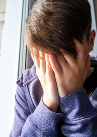 Sad Young Man close his Face with a Hands by the Window in the Room