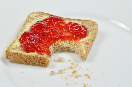 missing bite: Strawberry jam on Toast, missing Bite with Crumbs Stock Photo
