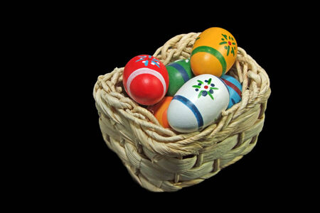 Colorful Easter Eggs in a Basket, isolated on Black, close up photo