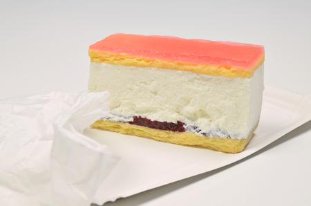 cream on cake: Un pedazo de pastel de crema con la bolsa de papel en la placa de papel, de cerca