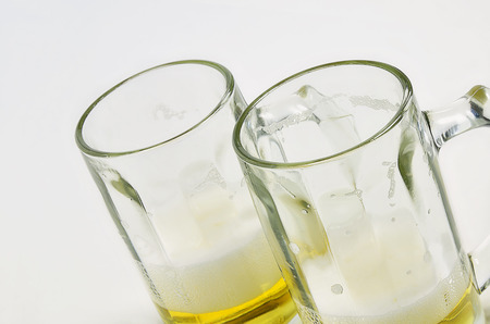 two and a half: close up of two beer mugs on a white background, half full, half empty, diagonal