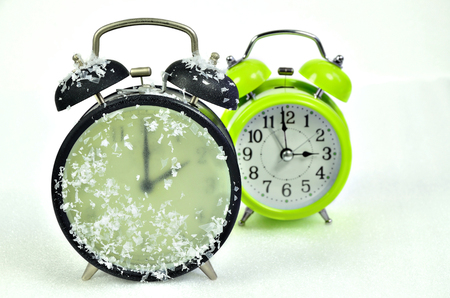 close up of two retro alarm clocks, black and green, showing wintertime and summertime, 2 am, 3 am, on white background, horizontal Stock Photo