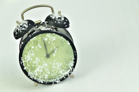 slanted: close up of a snowy black retro alarm clock, showing wintertime, 2 am, on white background, horizontal, slanted