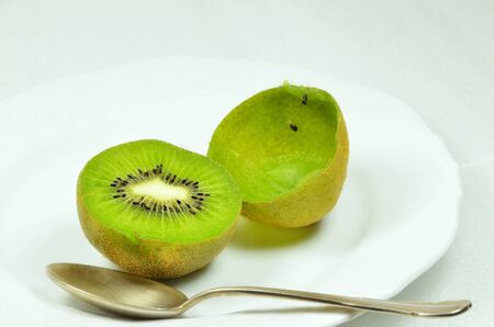 bisected: Two halved kiwi fruits, full and empty, on white plate with silver spoon, close up, macro, horizontal, white background