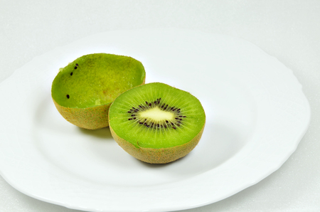 bisected: Two halved kiwi fruits, full and empty, on white plate, close up, macro, horizontal, white background