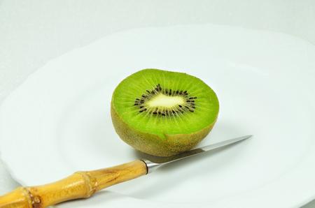 bisected: halved kiwi fruit with knife on white plate, close up, macro, horizontal, white background