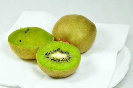 bisected: Three kiwi fruits, halved and whole, full and empty, on white plate, close up, macro, horizontal, white background