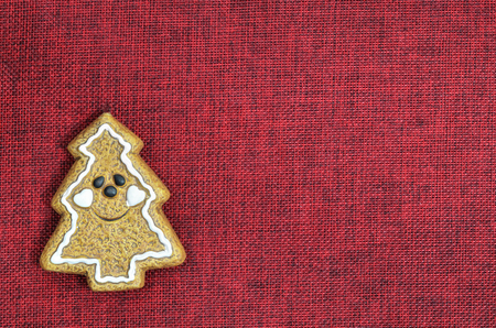 christmas ornamentation: close up of a Christmas cookie, Christmas tree, smiling, on red canvas with copy space, horizontal